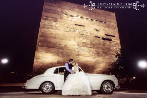 bride and groom kissing in front of perot museum wedding with vintage car at night
