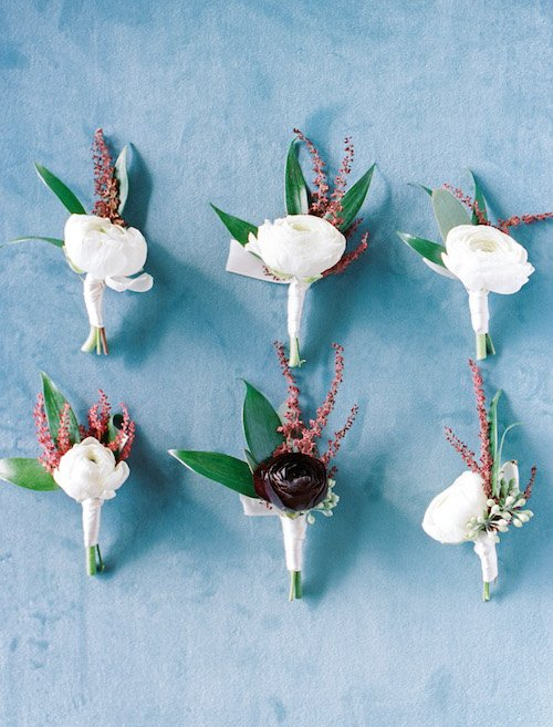 Simple, elegant ivory boutonnieres with a touch of burgundy with a pale blue back ground.