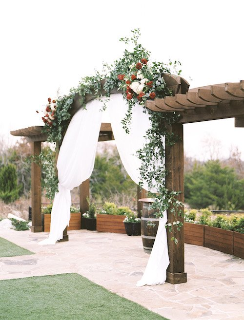 Romantic outdoor ceremony arch with white draping. Ivory and Burgundy flowers with trailing greenery sprawling across the arch at Stone Crest Venue.