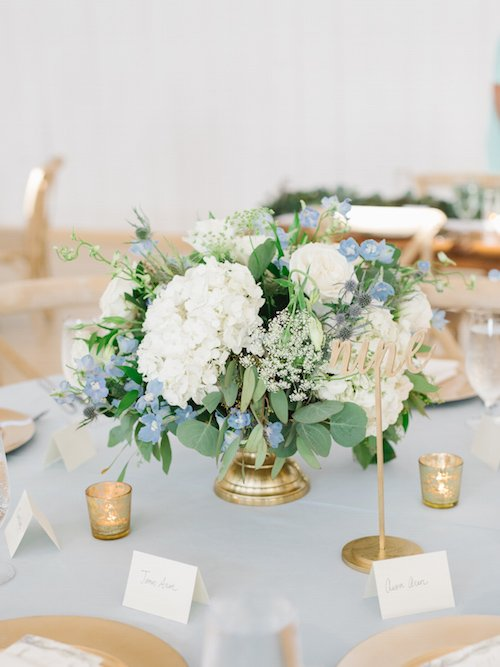 Romantic gold, ivory and pale blue centerpiece surrounded by romantic gold votives. Light and airy floral centerpiece.
