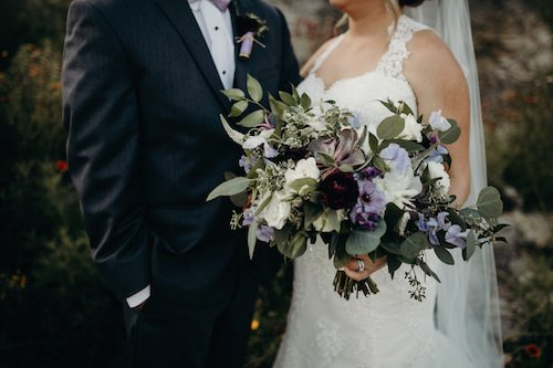 Bride and groom with rustic lavander and ivory bridal bouquet with wild greenery.