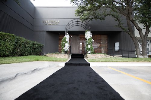 Knowing this, now you can see how they like the drama and how we brought it for them on wedding day.  We started simply with a black carpet runner to welcome guests instead of the traditional red.  Guests walked down the white corridor and came out in the modern ceremony room with a wall of clear acrylic pillars and vases that showed off the white floral as if it was floating.  The black and white runner for the aisle and the gold hanging lights are the perfect accents to the room. - Dallas, Texas - Hall on Dragon - Wedding Planner - Each & Every Detail