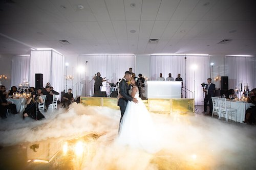 Once guests were seated, Jerrika & Taylor brought the drama by dancing their first dance while  Avery Wilson (from The Voice) performed and seemingly dancing on a cloud on their custom gold dance floor with monogram.  We love the romance of the cloud effect! - First Dance Wedding - Gold Dance Floor - Wedding Band - Wedding Planner - Each & Every Detail