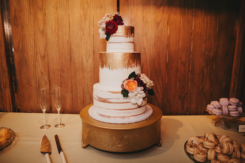 This cake fits so perfectly with the venue around it, which is especially impressive considering that this location was part of a rain plan. It really speaks to the importance of having a cohesive look throughout the event so that all of the elements are complementary no matter where in the venue they end up. Plus the gold paint with lush floral is amazing!