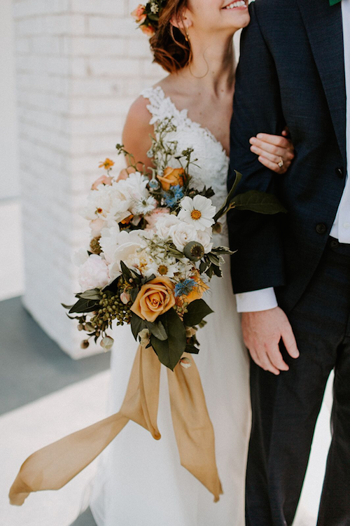 The loose greenery and pops of color in this bouquet really stood out amidst the clean ivory of the venue and brought out the radiance of this sweet couple. We still can't get over how that long ribbon billowed in the breeze. - McKinney Texas - Bridal Bouquet - Wedding Planner - Each & Every Detail