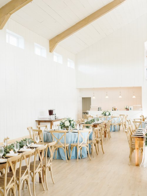Farm tables, white wood cross back chairs and dusty blue linens with simple floral and candle centerpieces created a soft and romantic feel for their reception. - Blue & Ivory Wedding - Reception - White Barn - The Grand Ivory - McKinney, Texas - Wedding Planner - Each & Every Detail