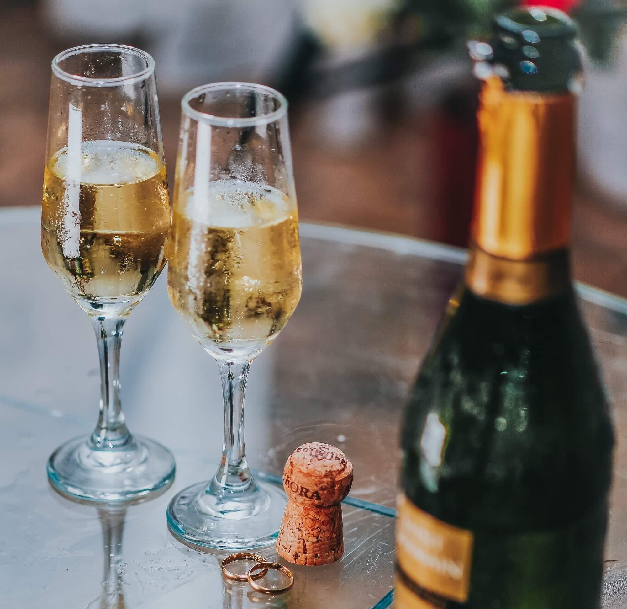 open-champagne-bottle-near-two-cocktail-glasses-1841506