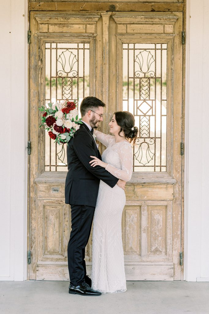McKinney, Texas - Texas Outdoor Wedding - Each & Every Detail - Mauve & Burgundy Wedding - Lush Greenery Wedding - Romantic Bride and Groom Photo - Ornate Wood Door Backdrop for Wedding